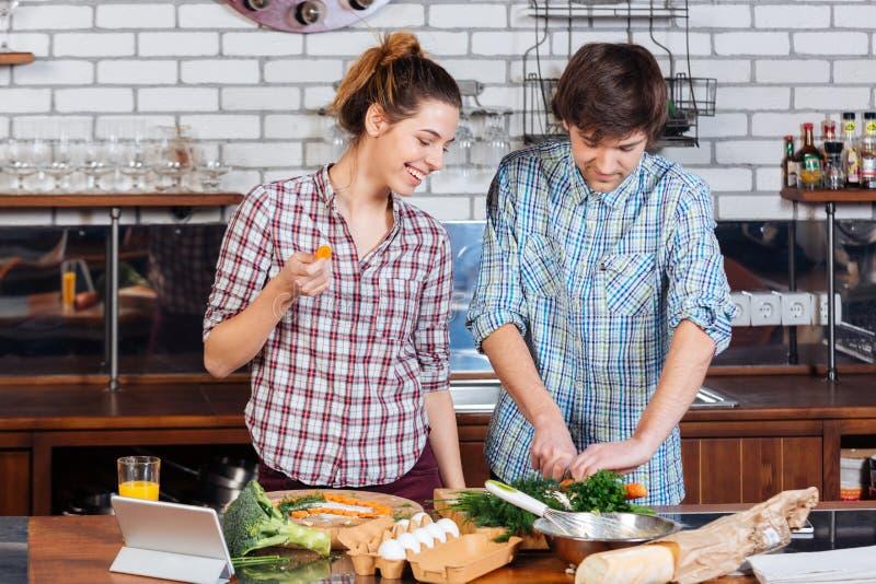 Beaux couples se tenant et faisant cuire ensemble sur la cuisine photo libre de droits