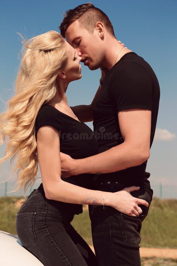 Beaux couples sexy dans des vêtements sport posant près de l'automobile photo libre de droits