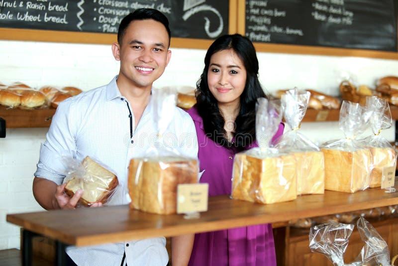 Beaux couples souriant à la boutique de boulangerie image libre de droits
