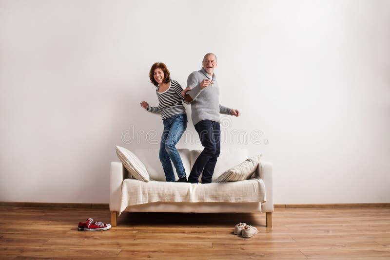 Beaux couples supérieurs se tenant sur le divan, dansant Projectile de studio image stock
