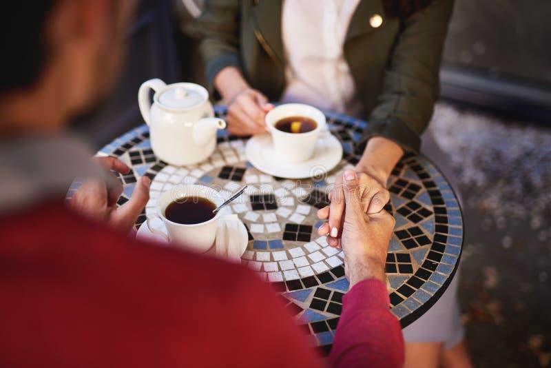 Beaux couples tenant des mains tout en passant le temps en café extérieur photo stock