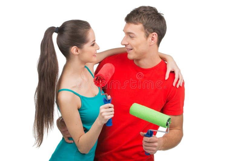Beaux couples tenant des rouleaux de peinture photographie stock libre de droits