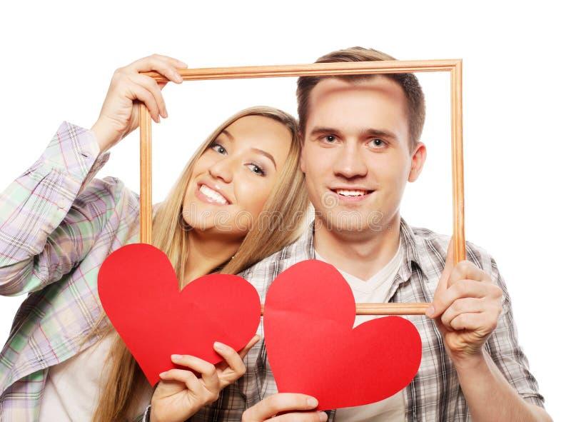 Beaux couples tenant le cadre et les coeurs rouges image stock