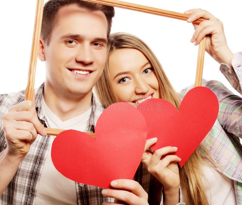 Beaux couples tenant le cadre et les coeurs rouges images stock