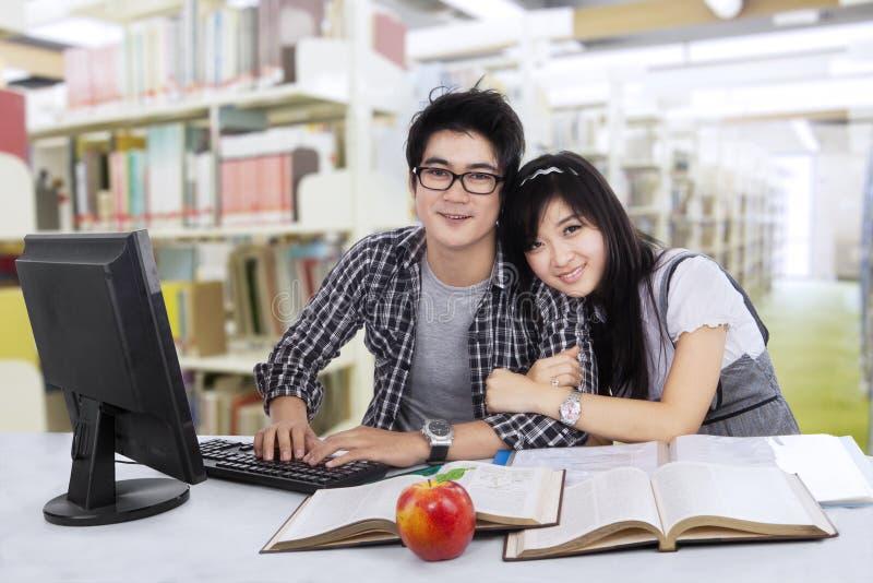 Beaux deux étudiants dans la bibliothèque images stock