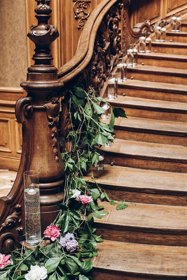 Beaux escaliers en bois décorés des fleurs et du cand de verdure photo stock