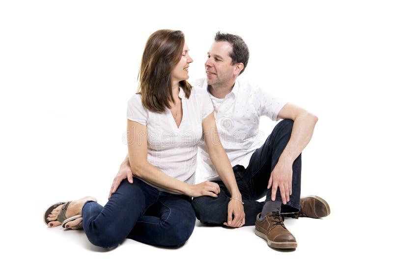 Beaux et gais couples se reposant sur le plancher photographie stock