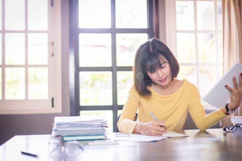 Beaux fonctionnement de femme d'affaires et note asiatiques d'écriture images stock