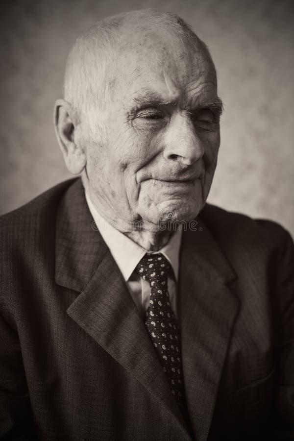 80 beaux homme supérieur an plus posant pour un portrait dans sa maison image stock