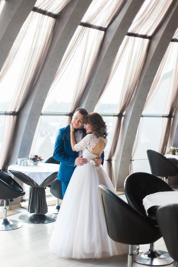 Beaux jeune mariée et fiancé dans le restaurant vide étreignant par les fenêtres image stock