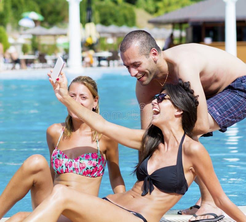 Beaux jeunes amis ayant l'amusement faisant le selfie sur la piscine images stock