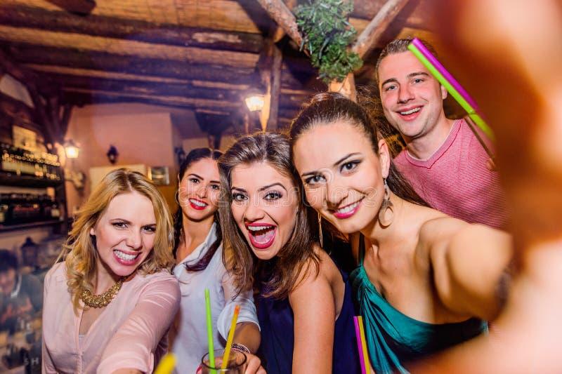 Beaux jeunes avec des cocktails dans la barre prenant le selfie images stock