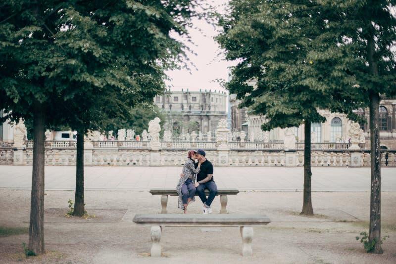 beaux jeunes couples élégants étreignant et embrassant sur le banc à Dresde photographie stock