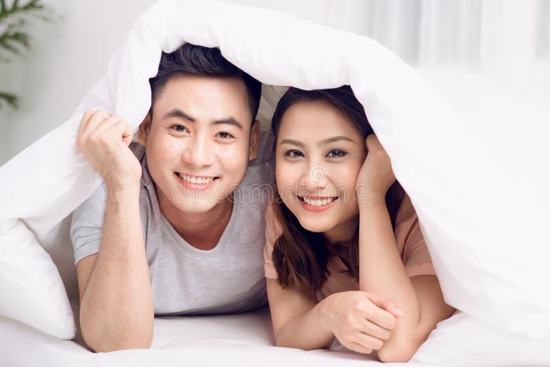Beaux jeunes couples affectueux se situant dans le lit ensemble image libre de droits