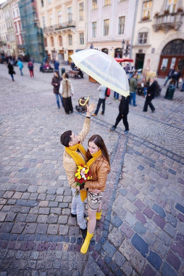 Beaux jeunes couples affectueux sous un parapluie sous la pluie photographie stock libre de droits