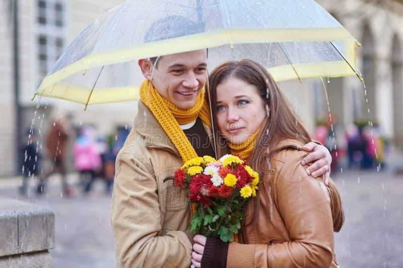 Beaux jeunes couples affectueux sous un parapluie sous la pluie image stock