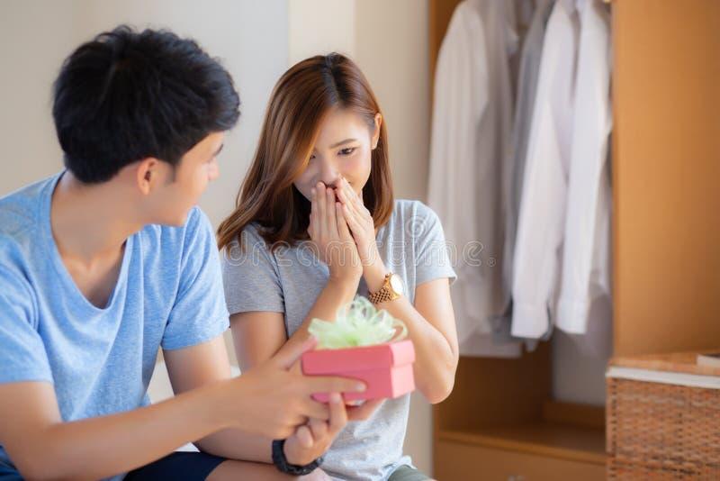 Beaux jeunes couples asiatiques dans le bo?te-cadeau de surprise d'amour dans la chambre ? coucher ? la maison photographie stock