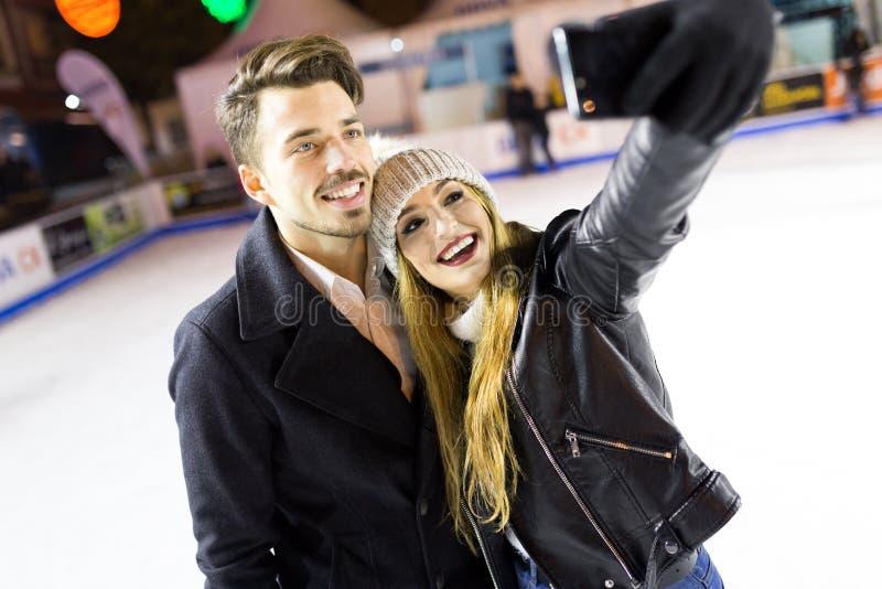 Beaux jeunes couples au moyen de eux téléphone portable sur le skatin de glace photo libre de droits