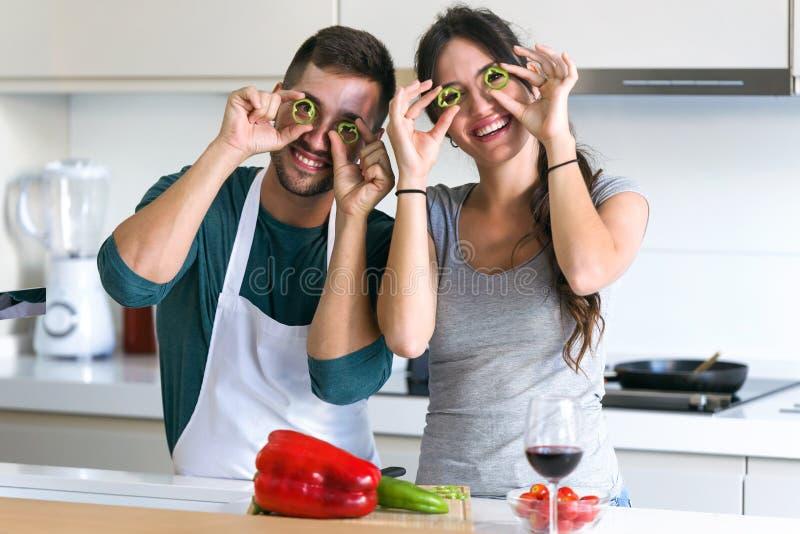 Beaux jeunes couples ayant l'amusement et jouant avec des tranches de poivrons sur les yeux dans la cuisine à la maison photos stock