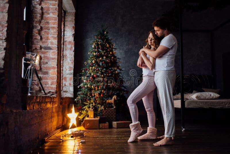 Beaux jeunes couples dans des pyjamas sur le fond bien décoré d'arbre de Noël images stock