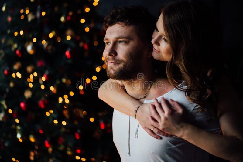 Beaux jeunes couples dans des pyjamas sur le fond bien décoré d'arbre de Noël image stock