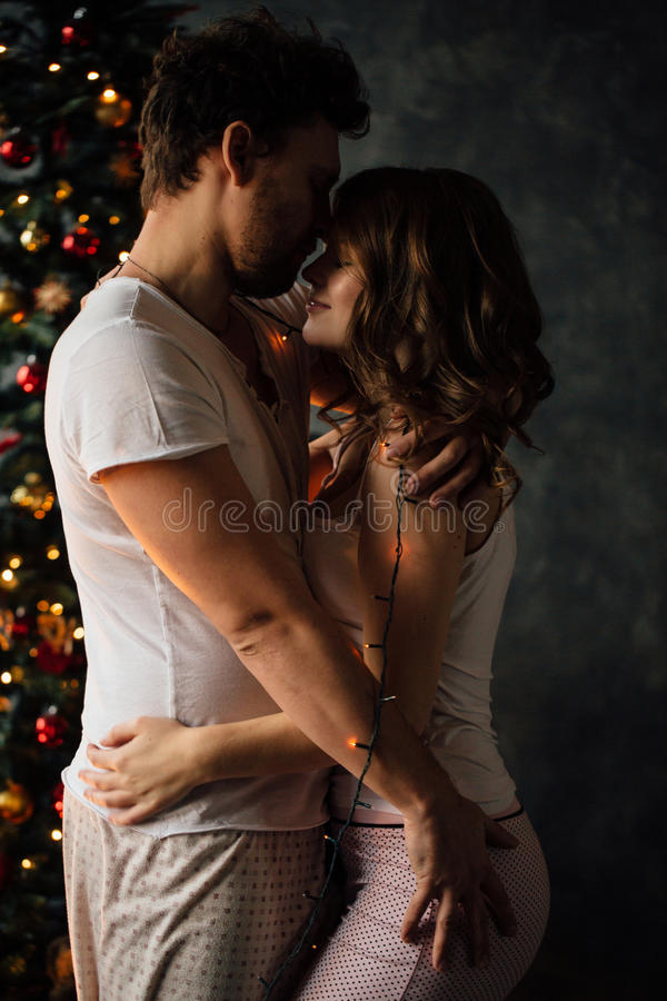 Beaux jeunes couples dans des pyjamas sur le fond bien décoré d'arbre de Noël images libres de droits