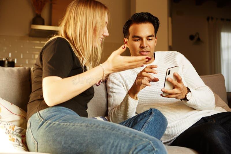 Beaux jeunes couples dans des vêtements sport utilisant le téléphone à la maison photo stock