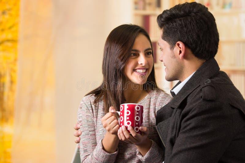 Beaux jeunes couples dans l'amour dans le jour de valentines de St, tenant une tasse de coffe se regardant à un arrière-plan brou photographie stock libre de droits