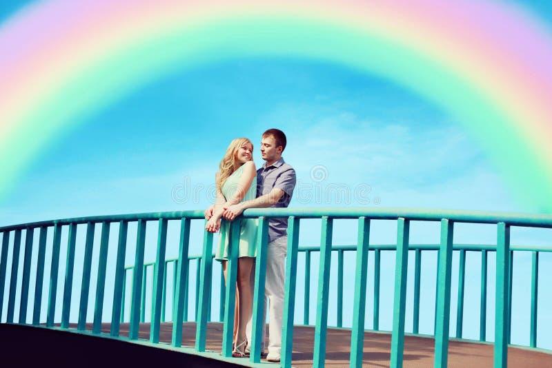 Beaux jeunes couples dans l'amour sur le pont au-dessus du ciel bleu photographie stock libre de droits