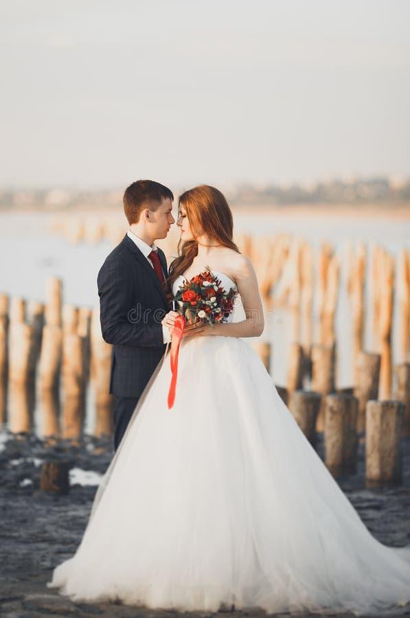 Beaux jeunes couples de mariage, jeunes mariés posant près des poteaux en bois sur la mer de fond photo libre de droits