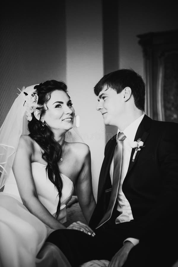 Beaux jeunes couples de photographie blanche noire se reposant sur le lit photo libre de droits