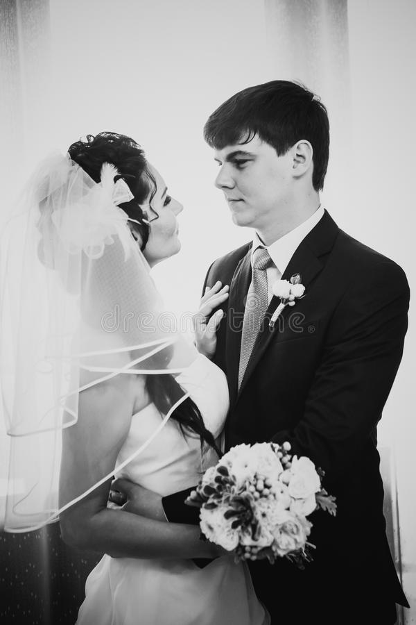 Beaux jeunes couples de photographie blanche noire se tenant près de la fenêtre photo libre de droits