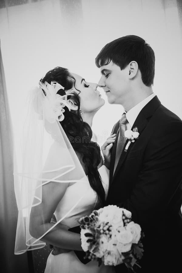 Beaux jeunes couples de photographie blanche noire se tenant près de la fenêtre image stock