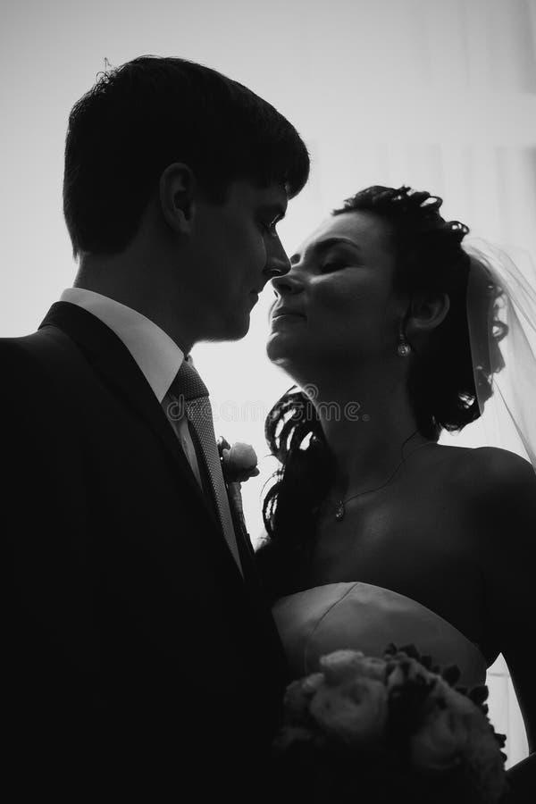 Beaux jeunes couples de photographie blanche noire se tenant près de la fenêtre photographie stock