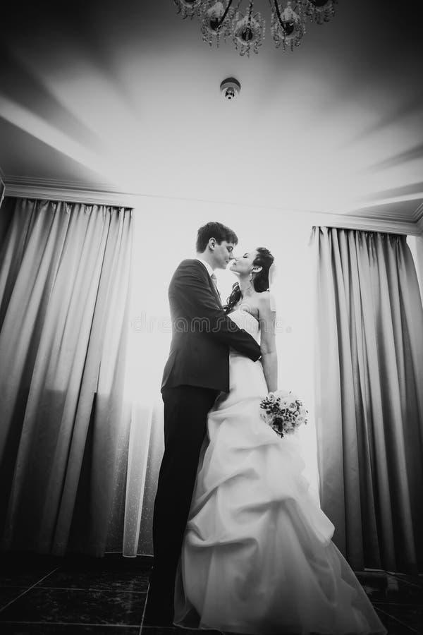 Beaux jeunes couples de photographie blanche noire se tenant près de la fenêtre photographie stock libre de droits