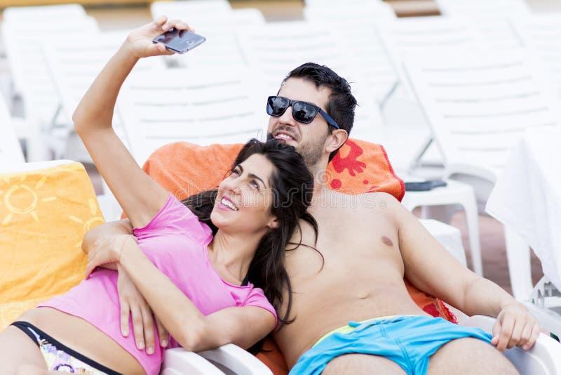 Beaux jeunes couples de sourire ayant l'amusement faisant le selfie photographie stock