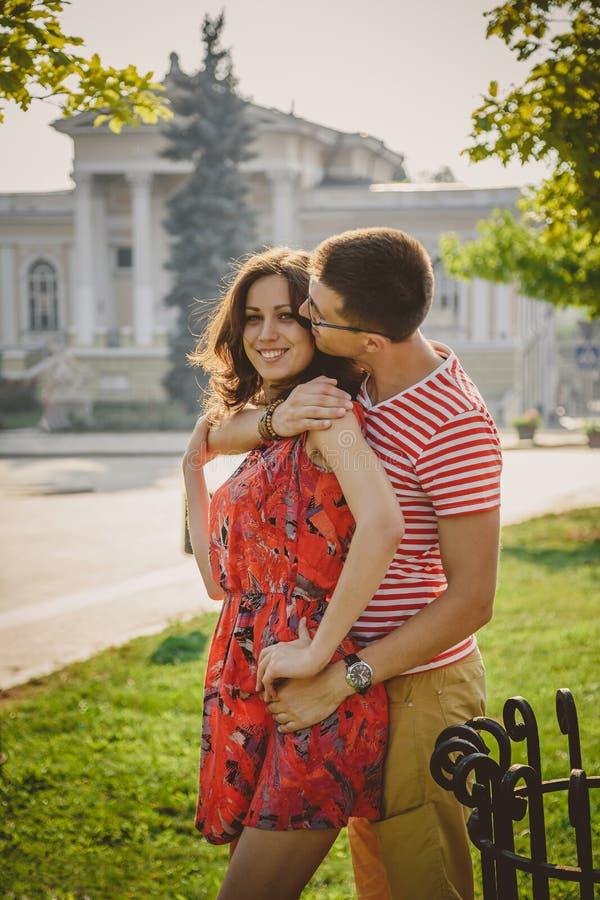 Beaux jeunes couples de sourire dans l'amour, étreignant, embrassant et passant le temps ensemble dehors à la rue verte de ville photographie stock