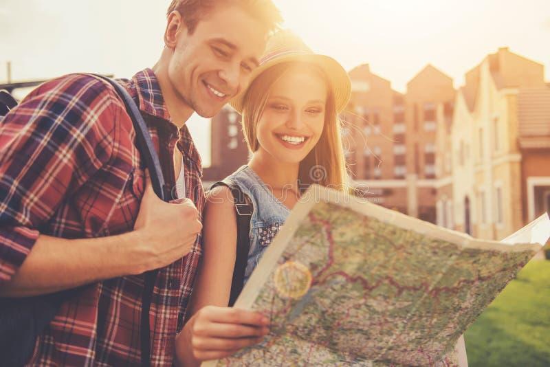 Beaux jeunes couples des voyageurs lisant la carte images libres de droits