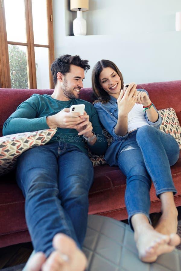 Beaux jeunes couples employant ils t?l?phone portable tout en se reposant sur le sofa ? la maison photographie stock libre de droits