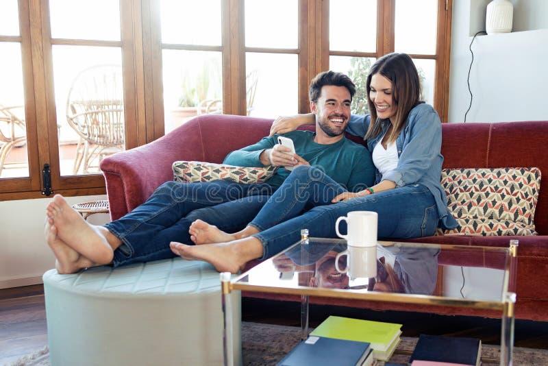 Beaux jeunes couples employant ils t?l?phone portable tout en se reposant sur le sofa ? la maison photographie stock