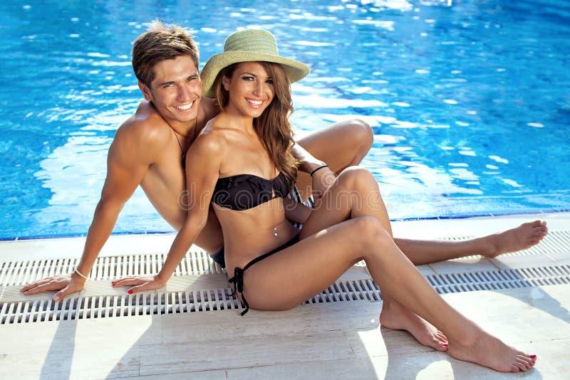 Beaux jeunes couples heureux à la piscine photo libre de droits