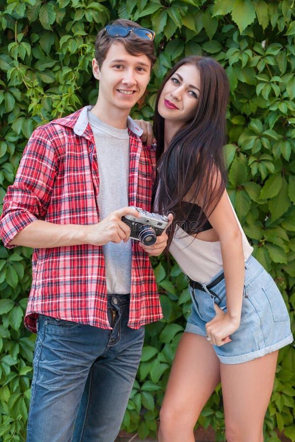 Beaux jeunes couples heureux près de mur vert avec l'appareil-photo regarder l'appareil-photo photo libre de droits