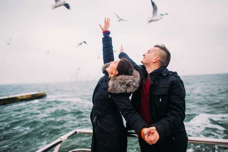 Beaux jeunes couples heureux tenant doucement des mains et posant sur le pilier Mouettes au fond Lune de miel romantique photos stock