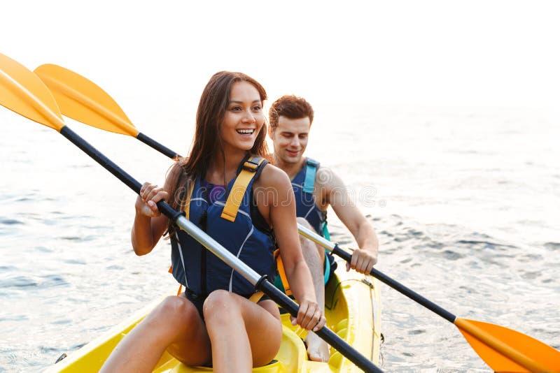 Beaux jeunes couples kayaking sur le lac ensemble images stock