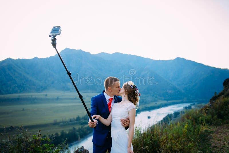 Beaux jeunes couples les ?pousant faisant le selfie sur le fond des montagnes et de la rivi?re photographie stock