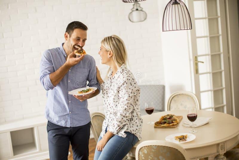 Beaux jeunes couples mangeant de la pizza image libre de droits