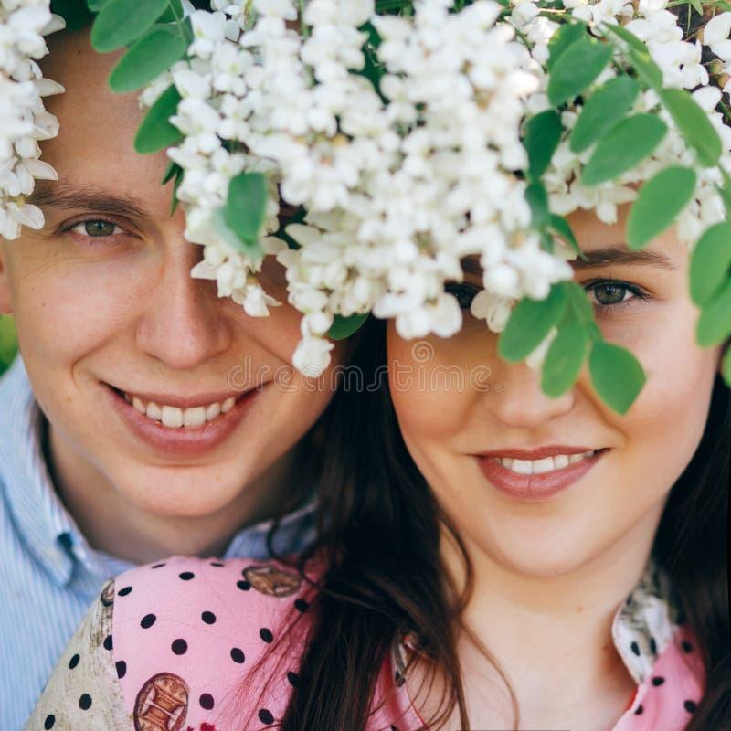 Beaux jeunes couples posant et souriant sous le jardin de fleurs blanches au printemps Portraits de famille heureuse embrassant à image stock