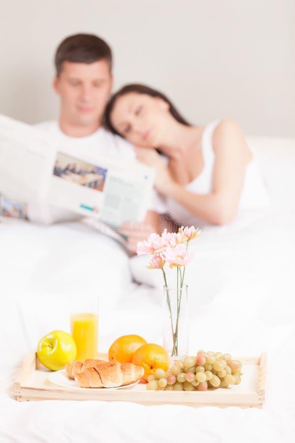 Beaux jeunes couples prenant le petit déjeuner photos stock