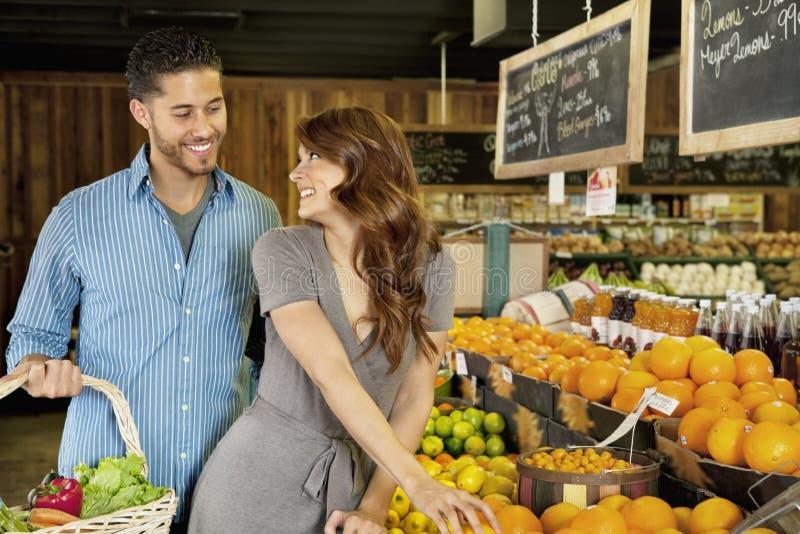 Beaux jeunes couples regardant l'un l'autre tout en faisant des emplettes dans le supermarché photos libres de droits