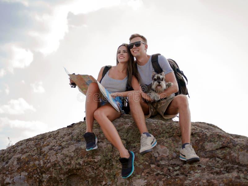 Beaux jeunes couples se reposant sur la roche et regardant la carte photographie stock libre de droits